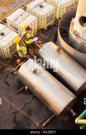 two petrochemical co-workers working in plant looking - Stock Photo