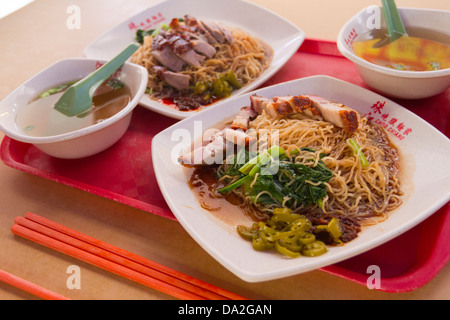 Two plates of Chinese food, one with roast duck and noodles, the other with crispy belly pork, Bugis, Singapore - Stock Photo