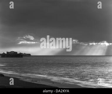 Sun rays over sea, dark sky and cloud, two piers, black and white, Brighton, UK - Stock Photo