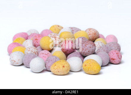 A shot of a pile of mini chocolate easter eggs on a plain white background. - Stock Photo