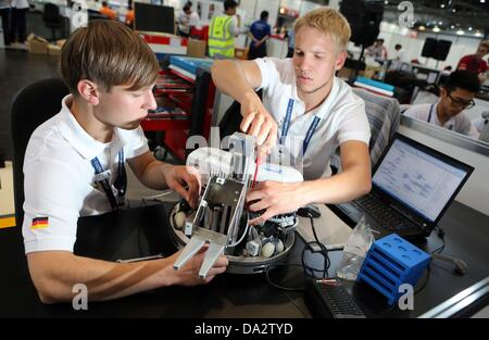 Germany's Thomas Kuehler (L) and Martin Richert  prepare for competition in the area of Mobile Robotics during the - Stock Photo