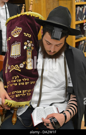 Jewish man praying while holding a Torah during morning services at Lubavitch headquarters in Crown Heights, Brooklyn, - Stock Photo