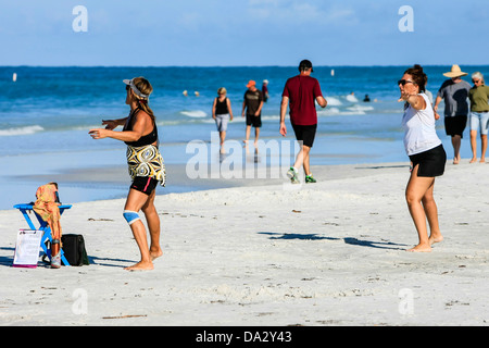 Women exercising the mind and body on the beach using the Nia technique - Stock Photo