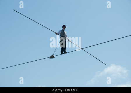 A tightrope walker walks overhead a crowd in the circus area of Glastonbury Festival of Contemporary Performing - Stock Photo