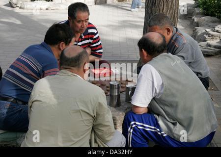 Chinese men sitting outdoors playing board game, Beijing, China - Stock Photo