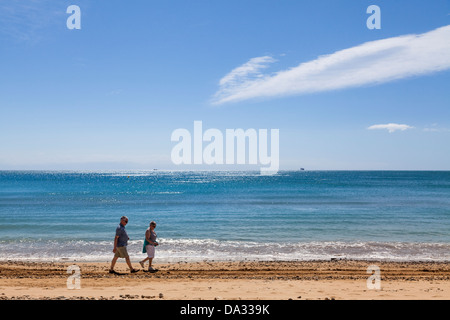 Middle aged couple walking along the waters edge on the beach.