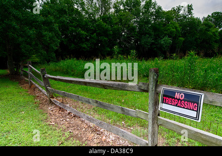 No trespassing sign on wooden fence in rural area. - Stock Photo