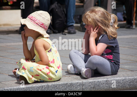 Two young girls sitting on pavement, one behind the other, during festival at Poole in June - Stock Photo