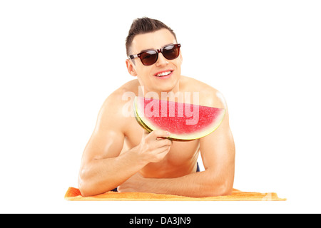 Young man laying on a beach towel and eating a slice of watermelon isolated on white background - Stock Photo