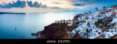 Panoramic shot at sunset over houses and villas at Oia Santorini Greece - Stock Photo