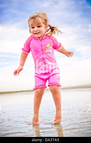 Little girl jumping in water on the beach - blond two year old toddler girl in pink swim suit - Stock Photo