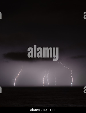 Lightning in distance over the sea at night - Stock Photo
