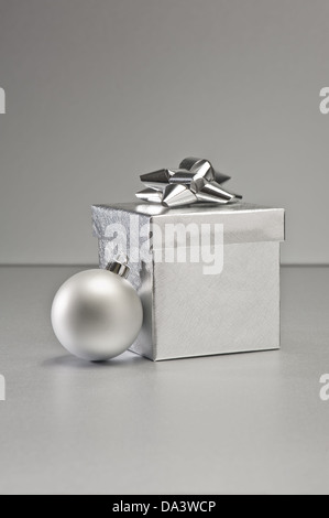 Silver bauble and present in Christmas setting - Stock Photo