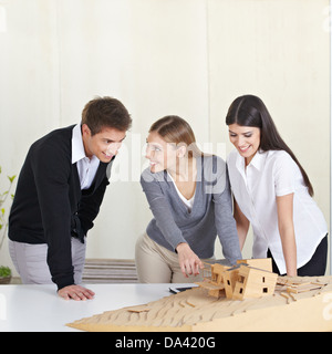 Three architecture students discussing 3D building model on desk - Stock Photo