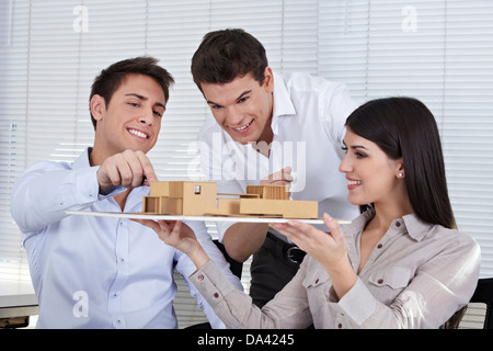 Three architects in their office discussing a building model - Stock Photo
