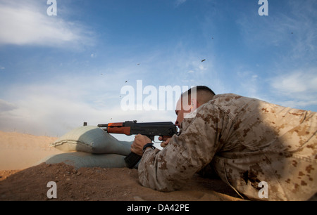 U.S. Marine Corps Sgt. Phillip Noble with Regimental Combat Team 7 engages his target during a foreign weapons and - Stock Photo