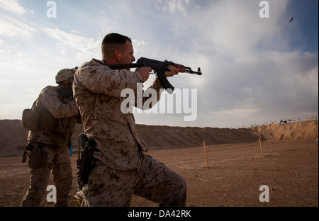 U.S. Marine Corps Sgt. Phillip Noble, right, with Regimental Combat Team 7 engages his target during a foreign weapons - Stock Photo