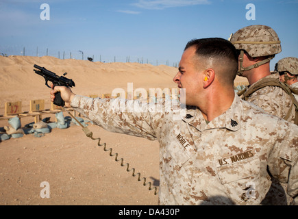 U.S. Marine Corps Sgt. Phillip Noble, left, with Regimental Combat Team 7 engages his target during a foreign weapons - Stock Photo