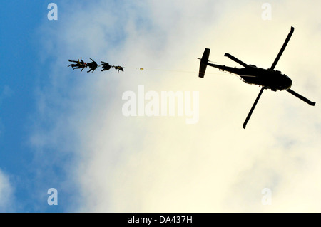 US Navy SEAL team members dangle from the Special Patrol Insertion and Extraction rope attached to an UH-60 Black - Stock Photo