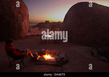 Sunset and campfire at campsite at Mowani Mountain Camp, near Twyfelfontein, Damaraland, Namibia, Africa - Stock Photo