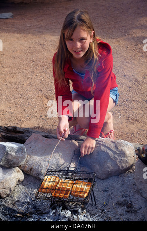 Girl cooking toast on a campfire at campsite at Mowani Mountain Camp, near Twyfelfontein, Damaraland, Namibia, Africa - Stock Photo