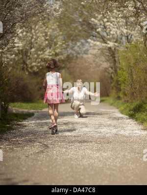 Young girl riding scooter in park away from camera to mother - Stock Photo