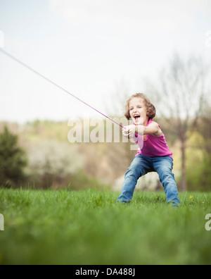 Young girl playing tug of war - Stock Photo