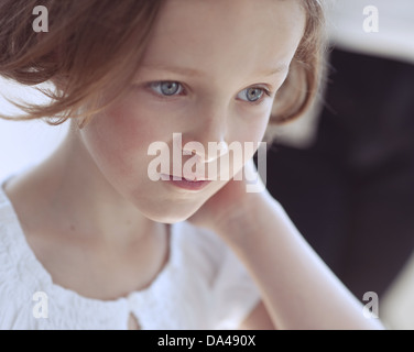 Close-up portrait of young girl looking away from camera - Stock Photo