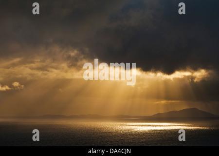 Evening light shining through dark stormy clouds onto the sea Scotland UK GB EU Europe - Stock Photo