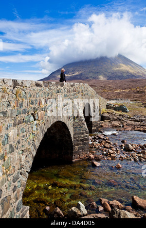 Woman stood on the old bridge at Sligachan over the river on the Isle of Skye Highlands and islands Scotland UK - Stock Photo