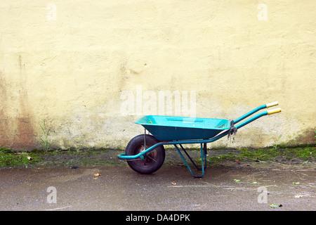 gardening wheelbarrow on a wall - Stock Photo