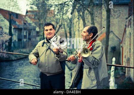 Street musicians entertaining tourists in Bruge, Belgium - Stock Photo