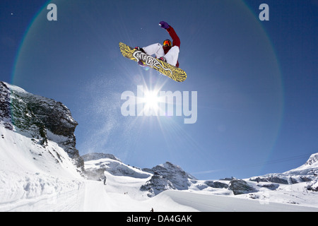 SAAS-FEE, VALAIS, SWITZERLAND. A female snowboarder riding the halfpipe with a stalefish trick. In the background - Stock Photo