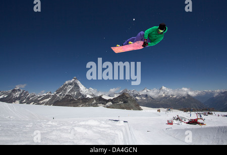 ZERMATT. A snowboarder riding the halfpipe with a backside double nose grab trick. In the background the Matterhorn - Stock Photo