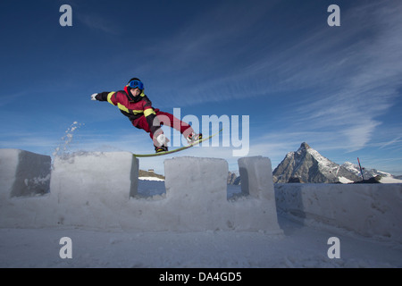 ZERMATT. A male snowboarder riding a castle wall made of snow with a tailpress trick. In the background the Matterhorn - Stock Photo