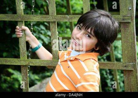 Brunette boy leaning on wooden fence in garden - Stock Photo