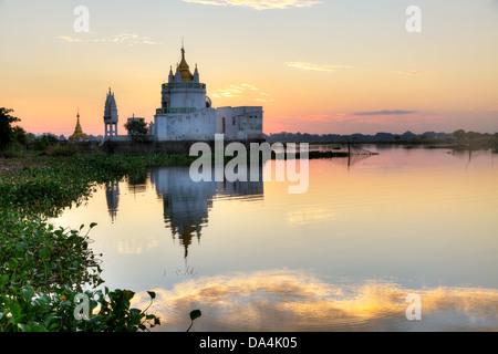 Buddhist temple at sunset reflecting in lake near U bein bridge at Amarapura ,Mandalay, Myanmar. - Stock Photo