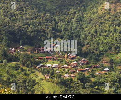 village with wooden huts with corrugated sheet iron metal roofs on a mountain slope in green jungle near Hpa An, - Stock Photo
