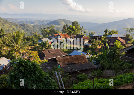 village with wooden huts and thatched roofs on a mountain slope in green jungle near Hpa An, Burma - Stock Photo