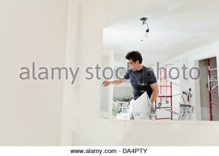 Tradesman plastering drywall with trowel in home - Stock Photo