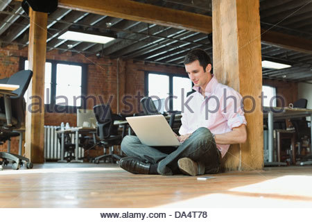 Entrepreneur working on laptop in creative office space - Stock Photo