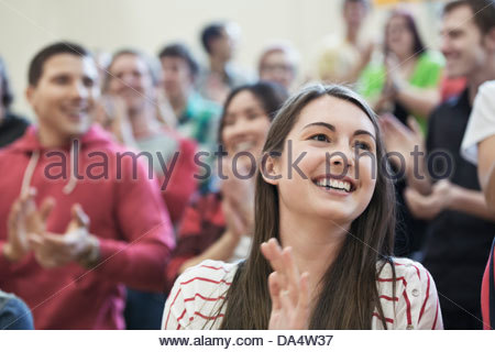 Female student clapping at college sporting event - Stock Photo
