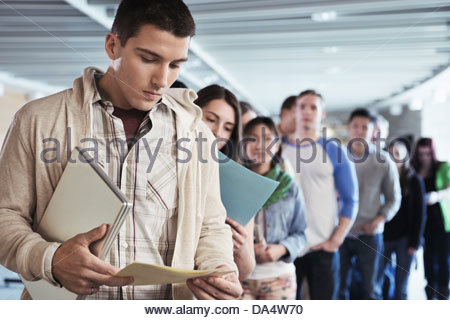 Large group of students standing in line at college campus - Stock Photo