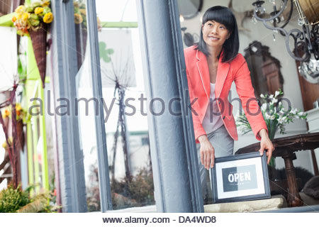 Female business owner displaying open sign in furniture store window - Stock Photo