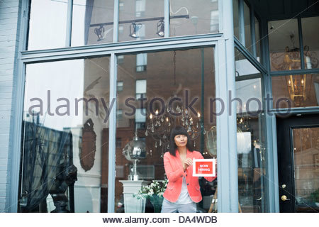 Female business owner displaying help wanted sign in furniture store window - Stock Photo