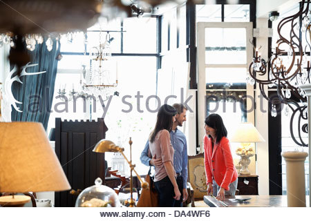 Female business owner helping customers in furniture store - Stock Photo