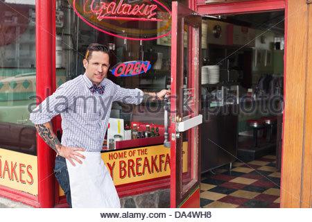 Portrait of male business owner opening diner door - Stock Photo