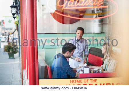 View through window of diner as owner takes customers orders - Stock Photo