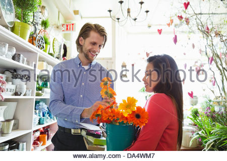 Female florist helping male customer in flower shop - Stock Photo