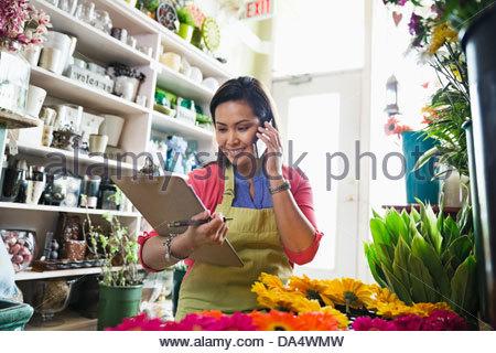 Female florist taking order on mobile phone in flower shop - Stock Photo